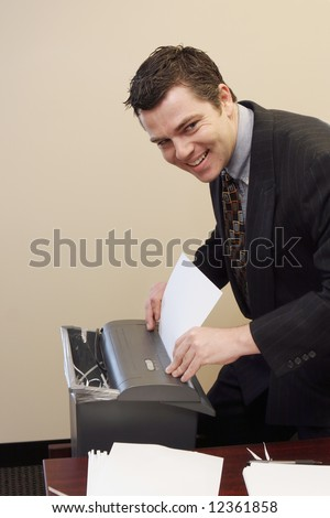 Caucasian businessman furtively shredding documents at his desk - stock photo