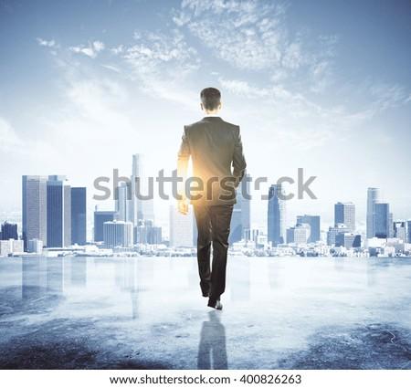 Caucasian businessman in black suit walking in city - stock photo