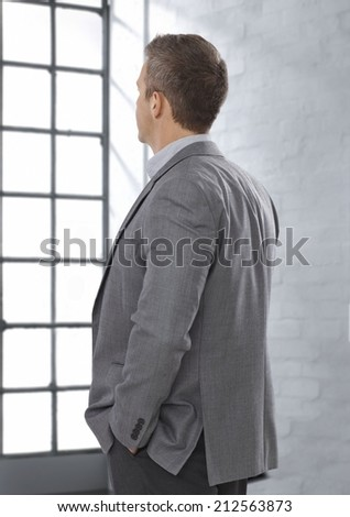 Caucasian businessman in suit looking at bright window, thinking, face not visible, hands in pocket. Decision, waiting. - stock photo