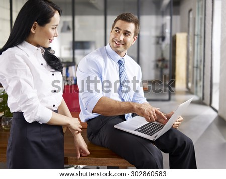 caucasian businessman pointing  to laptop screen while talking to his female asian coworker in office of a multinational company. - stock photo