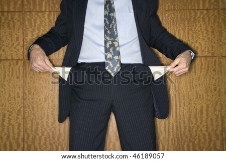Caucasian businessman's torso turning out his empty pockets. Horizontal shot. - stock photo