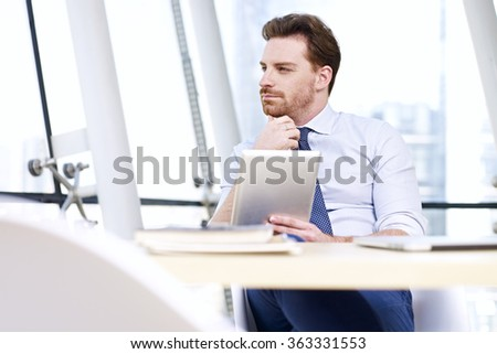 caucasian businessman sitting at desk thinking in office with tablet computer in hand. - stock photo