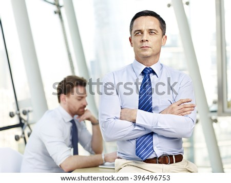 caucasian businessman sitting on desk arms crossed thinking contemplating in office with colleague in background. - stock photo