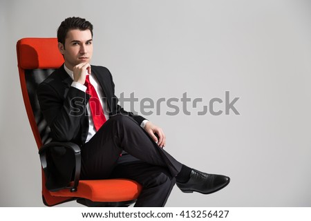 Caucasian businessman sitting on red sviwel chair with his legs cross and hand at chin - stock photo