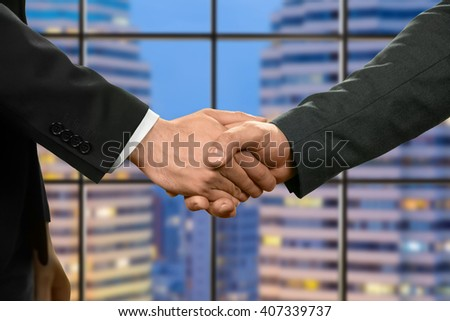 Caucasian businessmen shaking hands. Managers shake hands beside skyscraper. Productive day at work. Growth and development. - stock photo