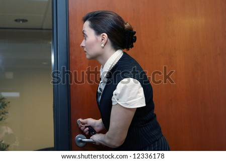 Caucasian businesswoman looking through a glass screen while working the lock on an office door - stock photo