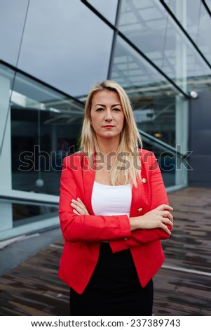 Caucasian businesswoman with arms crossed standing against her office building looking to the camera, blond hair executive business woman dressed in red jacket standing near skyscraper office building - stock photo