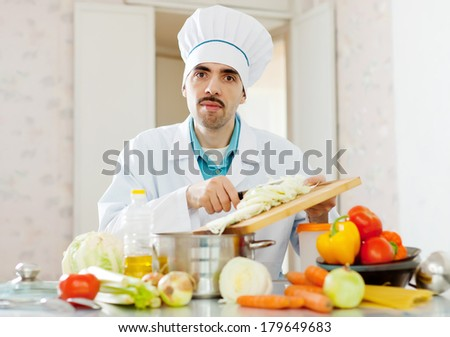 caucasian chef does veggie lunch at kitchen - stock photo