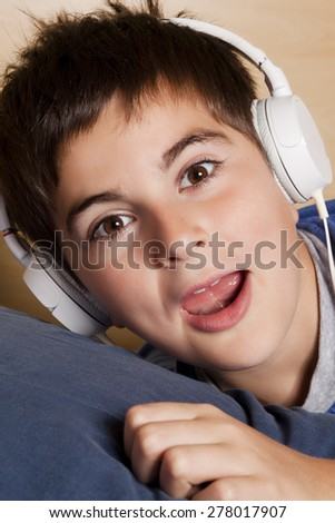 caucasian child listening music with headphones - stock photo