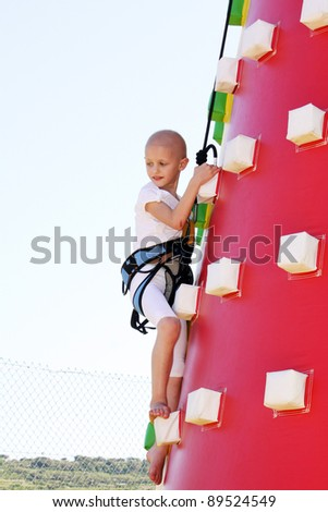 caucasian child undergoin treatment for cancer climbing a blow up castle at a fun fair - stock photo