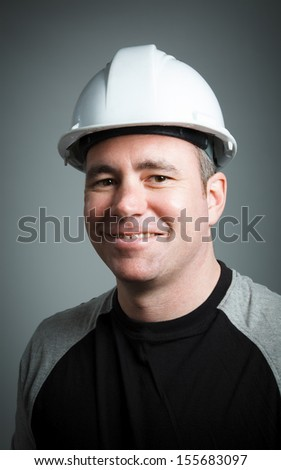 Caucasian contractor male 40 years old shot in studio isolated on grey background - stock photo