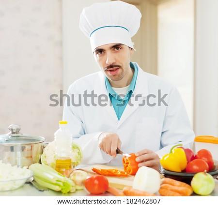 caucasian cook cuts red pepper on cutting board - stock photo