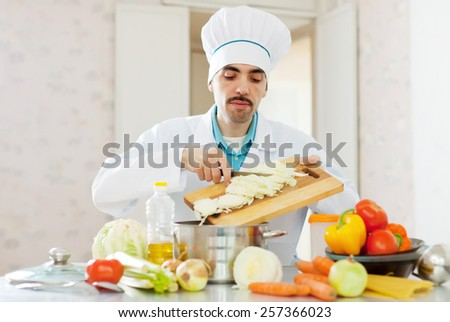 caucasian cook does veggy lunch at kitchen - stock photo