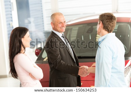 Caucasian couple purchasing a car in showroom - stock photo