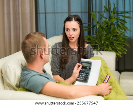 caucasian couple sitting on couch at home calculating payments - stock photo