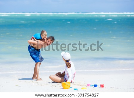 Caucasian couple with little son having fun on the beach - stock photo