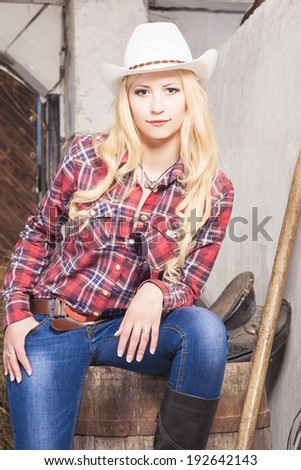 Caucasian Cowgirl In Stetson Sitting on Barrel on the Farm With Agricultural Stuff. Vertical Image - stock photo