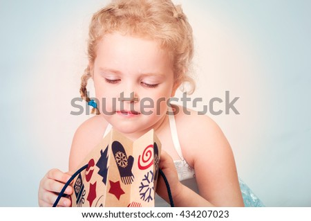 caucasian curly blond surprised girl in a ball gown in the New Year with Christmas snowflakes Christmas gift bags of brown paper - stock photo