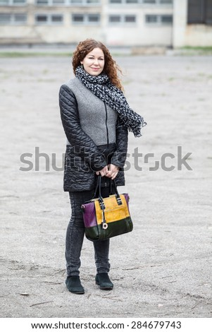 Caucasian curly hair woman holding bag in hand, looking at camera, full length portrait - stock photo