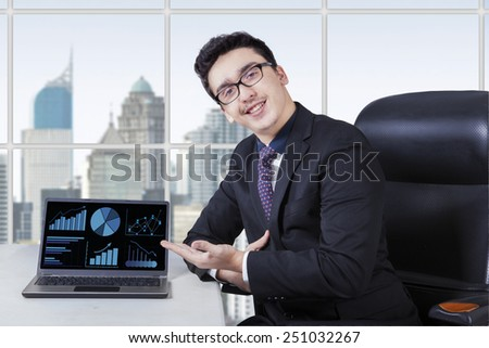 Caucasian entrepreneur presenting growing business chart with laptop in the office - stock photo