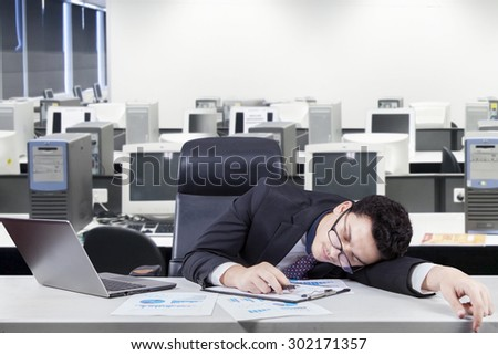 Caucasian entrepreneur sleeping on the table with laptop and financial chart. Shot in the workplace - stock photo