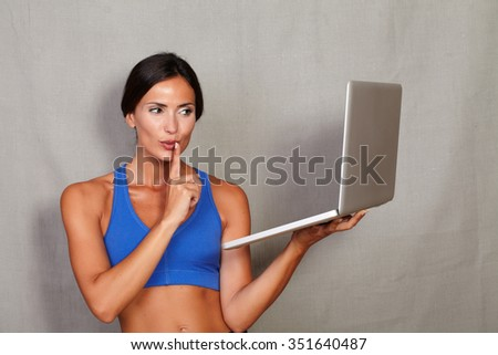 Caucasian ethnicity female gesturing keep quiet while holding laptop computer in gym clothing against grey texture background - stock photo
