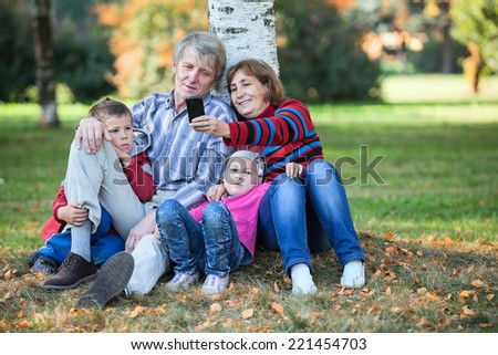 Caucasian family in park photographing on the cellphone. Selfie - stock photo
