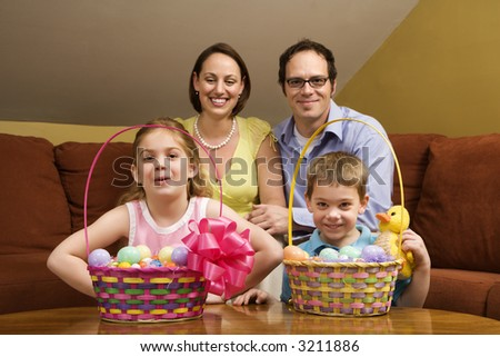 Caucasian family with Easter baskets looking at viewer. - stock photo