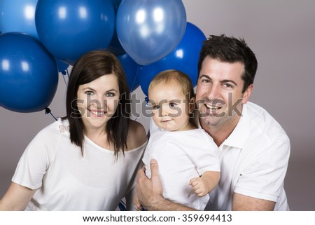 Caucasian family with mom dad and baby boy holding lots of blue helium balloons. Image is isolated on a white background. - stock photo