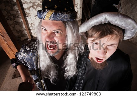 Caucasian father and son dressed as wizards shouting - stock photo