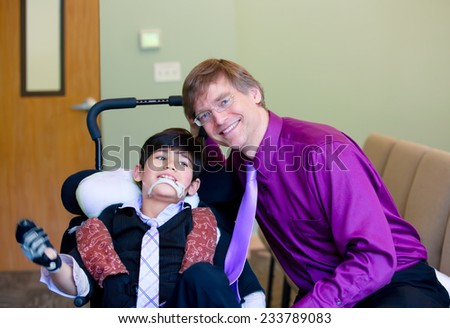Caucasian father in purple dress shirt and necktie sitting next to biracial disabled son in wheelchair - stock photo