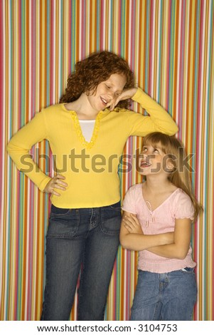 Caucasian female child leaning on smaller female child. - stock photo