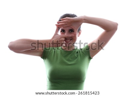 Caucasian female is looking at a subject through her fingers - stock photo