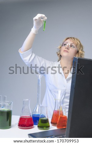 Caucasian Female Laboratory Worker During the Test. Isolated Over Gray. Vertical Image - stock photo