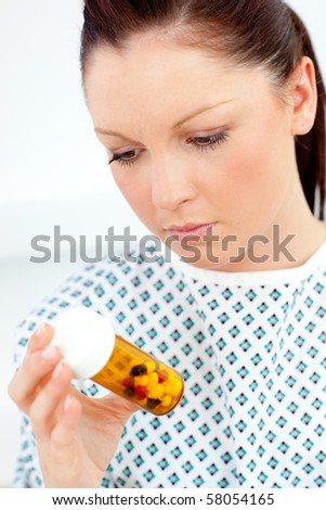 Caucasian female patient looking at pills against white background - stock photo