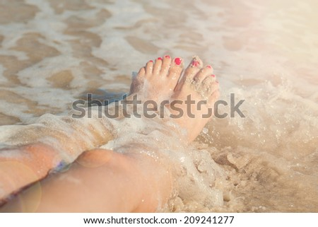 caucasian  girl beautiful  legs in sea with red nail polish on the nails - stock photo
