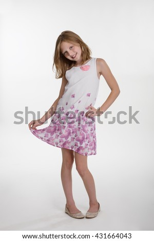 Caucasian girl in awesome dress of white color with pink flowers on it. Full body shot of a blonde little kid. Pleasant emotions and healthy smile. - stock photo