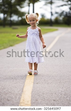 caucasian girl smiling and playing in the park - stock photo
