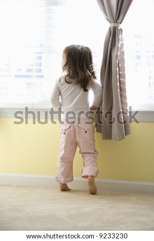 Caucasian girl toddler standing on tip toes looking out of window. - stock photo