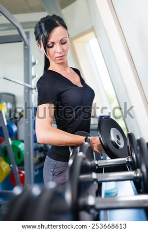 Caucasian girl with dumbbells in a gym. - stock photo