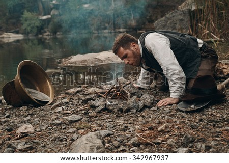 caucasian gold digger in retro clothes making fire after hard work. He wears shirt, leather pants and boots.  Sky is cloudy and grey. There is gold mining equipment in the frame. - stock photo
