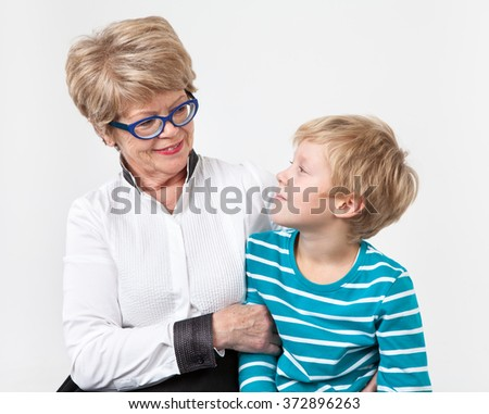 Caucasian grandmother and grandson together looking each other, portrait on a gray background - stock photo