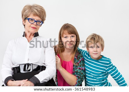 Caucasian grandmother, mother and son together looking at camera, portrait on a gray background - stock photo