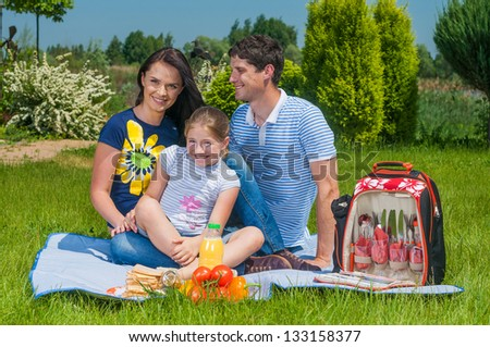 Caucasian happy family - mother, father and daughter having picnic in park. - stock photo