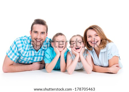 Caucasian happy smiling young family with two children lying down on the  floor - stock photo