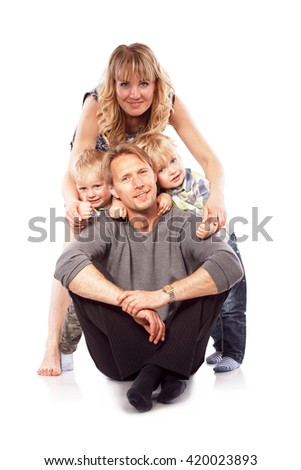 Caucasian happy smiling young family with two children sitting on the floor. Isolated on white. - stock photo