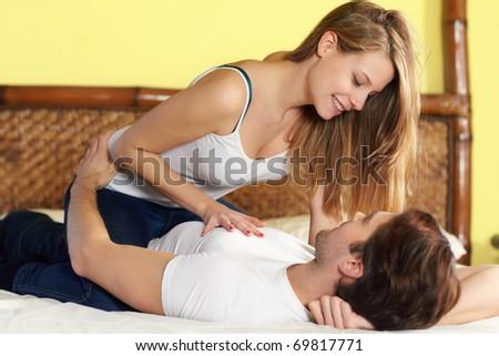 caucasian heterosexual couple flirting on bed. Horizontal shape, full length, side view - stock photo