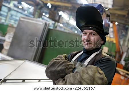 Caucasian industrial welder worker at factory workshop background - stock photo