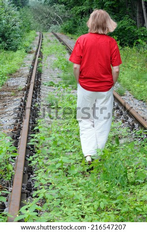 Caucasian lady walking away down abandoned railroad track - stock photo