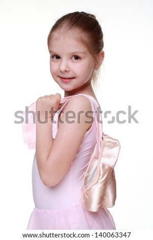 Caucasian little girl holding ballet shoes (pointes) - stock photo